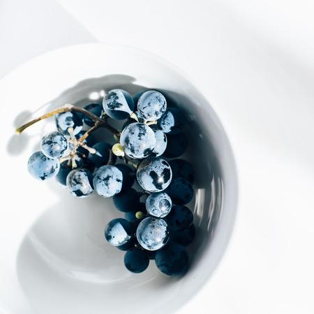 merlot: Merlot grape vine in white porcelain bowl on white table Stock Photo