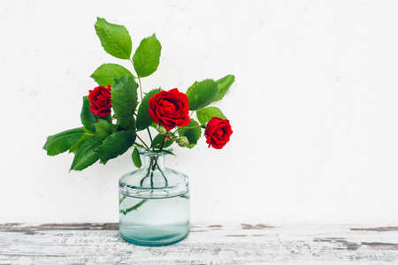 glass vase: Glass vase with bouquet of roses on vintage table