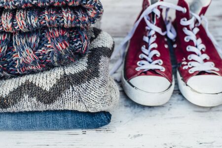 warm clothes: Warm clothes and trainers on wooden table