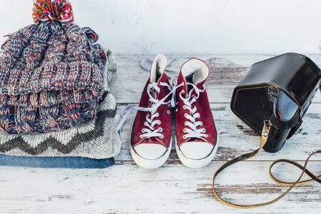 warm clothes: Warm clothes, trainers and film camera on wooden table