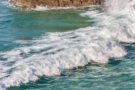 foamy: White foamy surf over green sea water