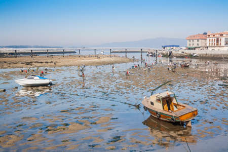 clam beds: Stranded boats and catching shellfish at low tide in Vilanova de Arousa