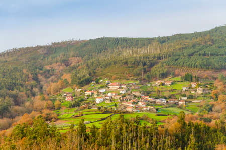 폰테 베 드라 (Pontevedra)와 오우 렌 세 지방 (Ourense provinces) 사이의 수도 (Suido) 산맥에서 숲으로 둘러싸인 마을 스톡 콘텐츠 - 77477455