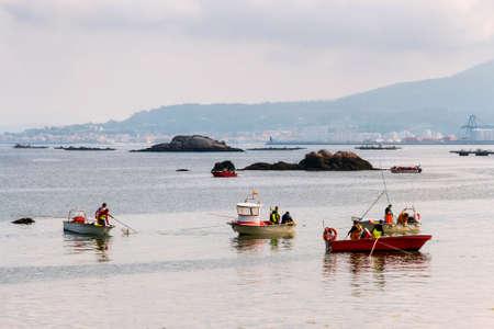 Sailors on four boats fishing clams on Sinas beach, Vilanova de Arousa