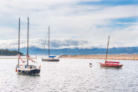 Three sailboats anchored on Xufre port, Arousa Island, wit Curota Mount covered by a clouds blanket at background Stock Photo