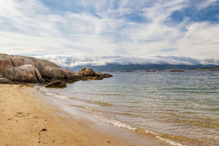 ocean waves: Rocks on Aguiuncho beach, Arousa Island, with blanket cloud covering Curota Mount at background
