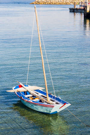 Samall wooden sailboat anchored on Cangas de Morrazo harbor