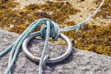 Sailor knot on stainless steel ring in the fishing harbor