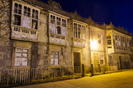 Facade of abandoned and ruined modernist houses of the old canning makers in Arousa Island at night