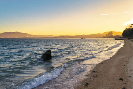 Rock and waves on Sinas beach, Vilanova de Arousa, at golden dawning