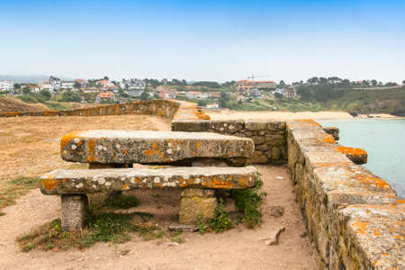 Stone table and bench in the wall of the enclosure of the chapel of Our Lady of La Lanzada with views from Foxos beach in Sanxenxo