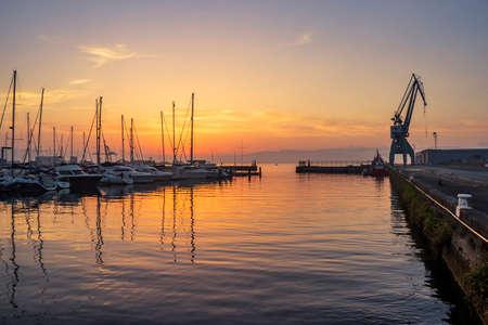 Moored boats and crane on Vilagarcia de Arousa harbor at golden evening Фото со стока