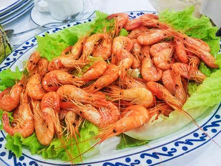 Palaemon serratus de camarón cocido servido en bandeja sobre hojas de lechuga