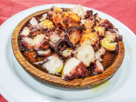 Wood plate with pieces of octopus tentacles on fair sauce