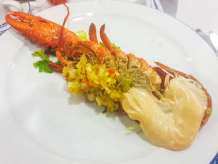 Half lobster with mayonnaise sauce served on porcelain plate