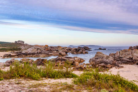 Granite coastal rocks in San Vicente of O Grove with Ons Island at background Archivio Fotografico