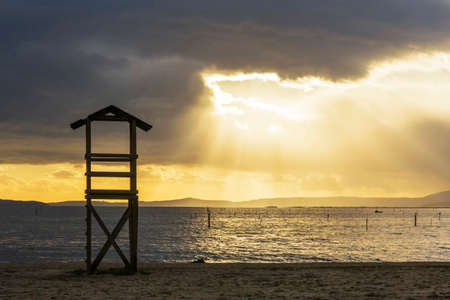 Sunbeams emerging between stormy clouds at sunset on Compostela beach in Vilagarcia de Arousa