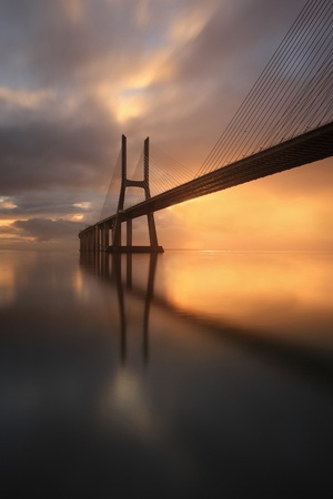 The Vasco da Gama Bridge over the river Tejo in Lisbon and is one of the largest bridges in europe  More than a bridge, is one of the attractions of Portugal, very contemplated the sunrise