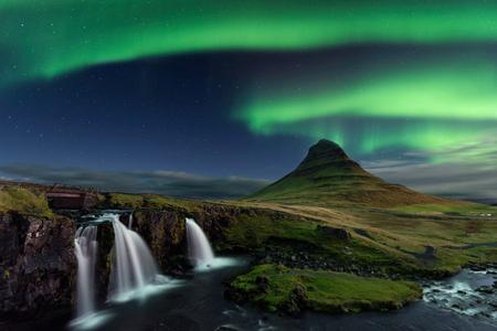 A luz do norte na montanha Kirkjufell Islândia. Paisagem da cachoeira Kirkjufellsfoss, com faixas verdes da Aurora Borealis.