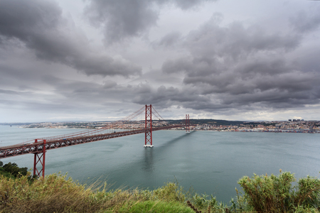 25th of April Bridge, Lisbon, Portugal. This bridge connects the two banks of the Tagus River between Lisbon and Almada. Panoramic landscape