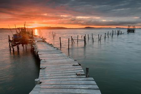 Zonsonderganglandschap van ambachtelijke vissersboten in de oude houten pijler. Carrasqueira is een toeristische bestemming voor bezoekers van de kust van Alentejo bij Lissabon.