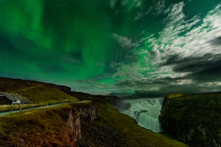 Northern Lights over the Gullfoss waterfall in Iceland. Aurora Borealis in an amazing nightscape. Travel destination with beautiful green lights landscape.