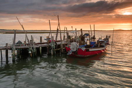Sunset landscape of artisanal fishing boats in the old wooden pier. Carrasqueira is a tourist destination for visitors to the coast of Alentejo near Lisbon.