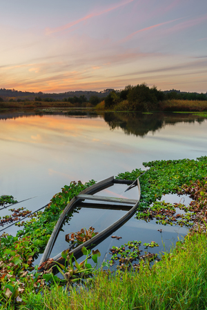 Natural landscape with boats in the water at sunset. Amazing lake with small artisanal fishing boats. Sunrise light reflected in water, mirror effect. Tourist attraction in Portugal. 版權商用圖片