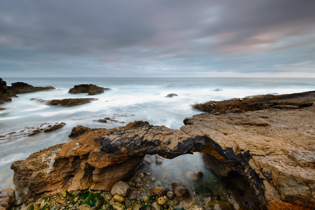 Seascape in Cascais Portugal. Stone bridge carved by the tides. Coastal landscape near Lisbon. Long exposure on a stormy day.