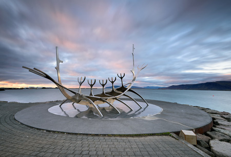 Icekand, Solfar at sunset. Sun Voyager monument, landmark of Reykjavik city with sea and mountains in background, Iceland Stock fotó
