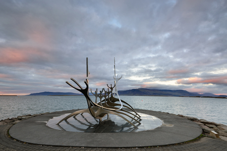 Icekand, Solfar at sunset. Sun Voyager monument, landmark of Reykjavik city with sea and mountains in background, Iceland 版權商用圖片 - 117133333