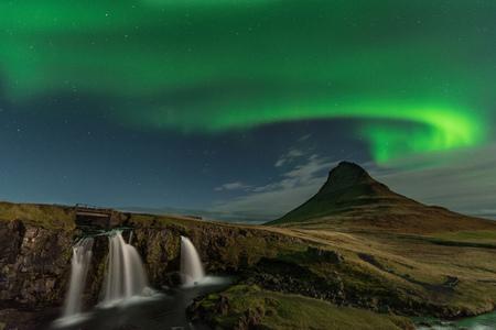 The Northern Light at the mountain Kirkjufell Iceland. Landscape of waterfall Kirkjufellsfoss, with green bands of Aurora Borealis. Snaefellnes, Iceland 版權商用圖片 - 117133335