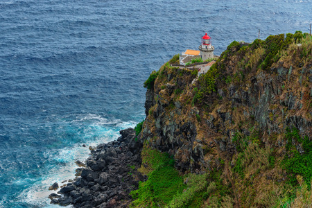 Historic lighthouse on the northeast coast of the island of S?o Miguel in the Azores. Landmark built on the cliff with a path to the sea and a small fishing port. Tourist attraction of Portugal. 版權商用圖片 - 122978584