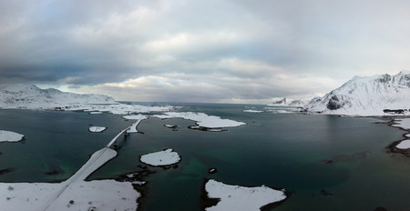 Aerial drone panoramic view of amazing Lofoten Islands winter scenery with famous Reine fishing village Norway, Scandinavia. Top view picture at sunset.