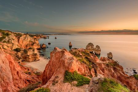 Amazing landscape at sunrise. Beautiful beach near Lagos in Ponta da Piedade, Algarve region, Portugal. Seascape with Cliff rocks. 版權商用圖片 - 122978594