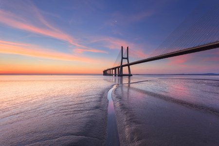 Vasco da Gama Bridge landscape at sunrise. One of the longest bridges in the world. Lisbon is an amazing tourist destination because its light, its monuments. Portugal landmark. 版權商用圖片 - 122978599