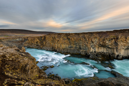Aldeyjarfoss waterfall in Iceland at sunrise with golden clouds in the sky. Amazing landscape in beautiful tourist attraction. Wonder of nature with glacier water.