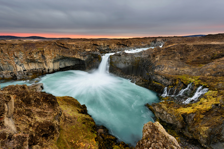 Aldeyjarfoss waterfall in Iceland at sunrise with golden clouds in the sky. Amazing landscape in beautiful tourist attraction. Wonder of nature with glacier water. 版權商用圖片 - 122978603