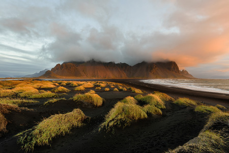 Magical landscape of Vestrahorn Mountains and Black sand dunes in Iceland at sunrise.  Panoramic view of the Stokksnes headland in a Colorfulseascape. 版權商用圖片 - 122978619