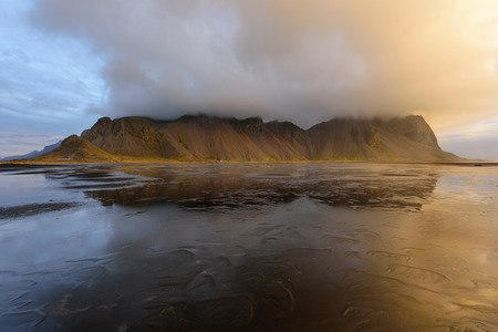Magical landscape of Vestrahorn Mountains and Black sand dunes in Iceland at sunrise.  Panoramic view of the Stokksnes headland in a Colorfulseascape. 版權商用圖片 - 122978620