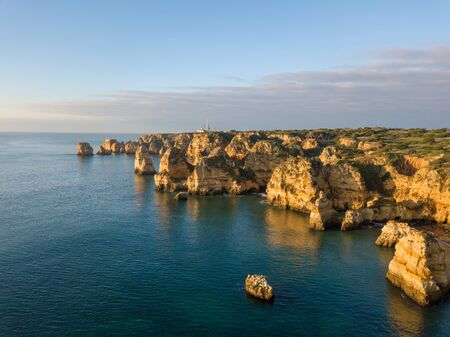 Algarve aerial drone panoramic view. Amazing landscape at sunrise. Beautiful beach near Lagos, Algarve region, Portugal.  Seascape with cliff rocks. 版權商用圖片 - 126434132