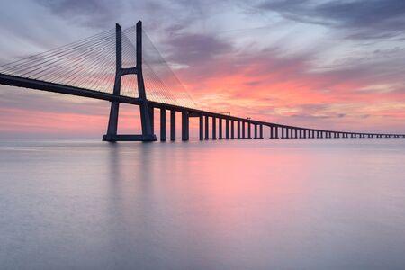 Vasco da Bridge landscape at sunrise. One of the longest bridges in the world. Lisbon is an amazing tourist destination because its light, its monuments. Portugal landmark.