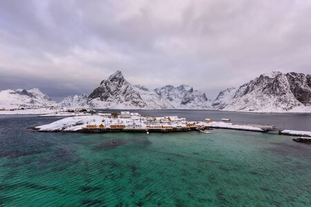 Typical Norwegian landscape. Beautiful view of scenic Lofoten Islands winter scenery with traditional yellow fisherman Rorbuer cabins in the historic village of Sakrisoy at sunset, Norway, Scandinavia 版權商用圖片 - 126434137