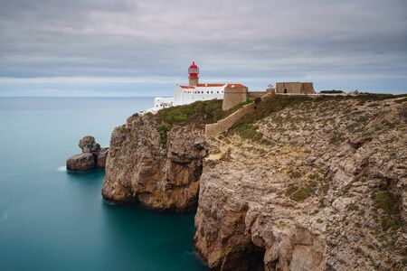 Landscape of the lighthouse and cliffs at Cape St. Vincent at sunset. Algarve amazing seascape.  Continental Europes most South-western point, Sagres, Portugal. Stock fotó