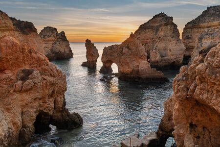 Amazing landscape at sunrise. Beautiful beach near Lagos in Ponta da Piedade, Algarve region, Portugal.  Seascape with Cciff rocks. 版權商用圖片 - 129589599