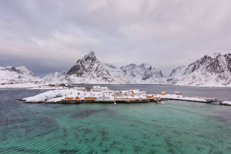 Typical Norwegian landscape. Beautiful view of scenic Lofoten Islands winter scenery with traditional yellow fisherman Rorbuer cabins in the historic village of Sakrisoy at sunset, Norway, Scandinavia