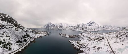 Aerial drone panoramic view of amazing Lofoten Islands winter scenery with famous Reine fishing village Norway, Scandinavia. Top view picture at sunset. 版權商用圖片 - 129590956
