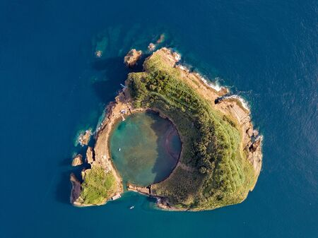Azores aerial panoramic view. Top view of Islet of Vila Franca do Campo. Crater of an old underwater volcano. San Miguel island, Azores, Portugal. Heart carved by nature. Bird eye view.