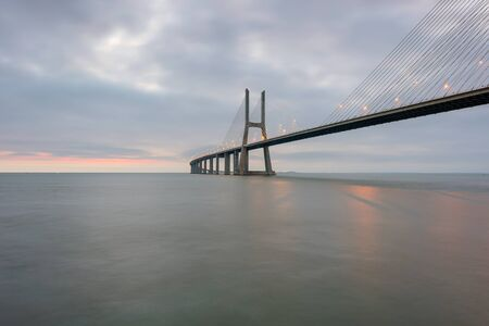 Urban landscape at sunrise. Lisbon is an amazing tourist destination. The Vasco da Gama Bridge is a beautiful landmark, and one of the longest bridges in the world. Portugal in a dawn light.