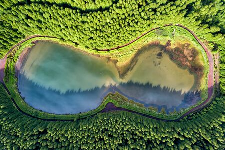 Glasses shaped drone landscape. Top down aerial view of a small pond in the middle of a forest, reflecting clouds in the sky. Bird view of Empadadas lagoon in Azores, Portugal. 版權商用圖片 - 129591102